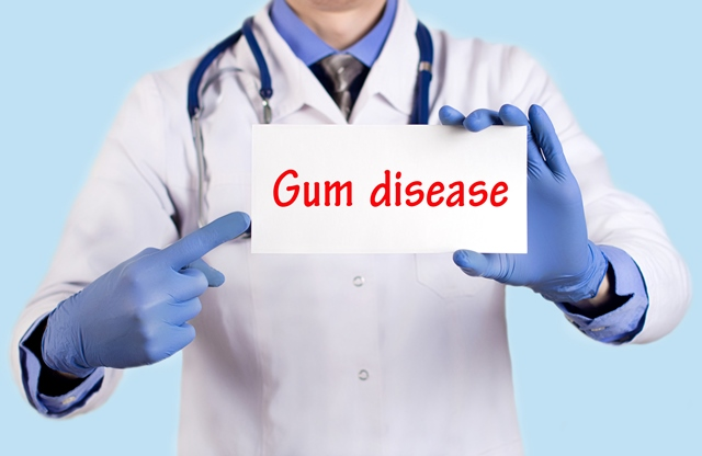 Doctor pointing to a card that reads gum disease