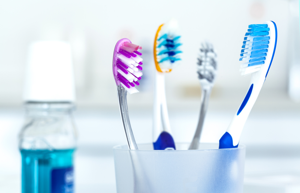 Toothbrushes in glass in bathroom. Mouthwash blurry in background.