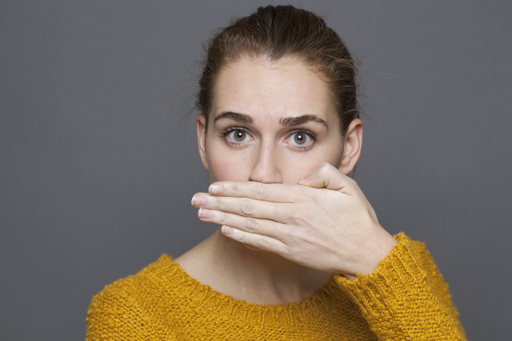 Woman with bad breath covers her mouth