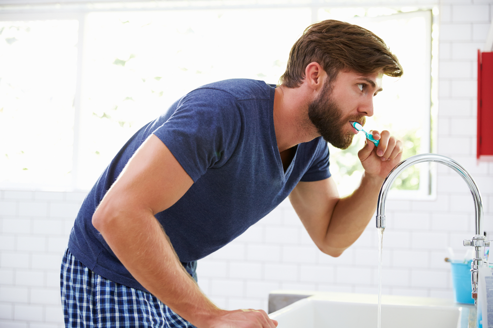 Handsome bearded man brushing teeth in bathroom in morning in pyjamas.