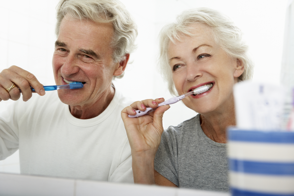 Senior couple in bedroom brushing their teeth